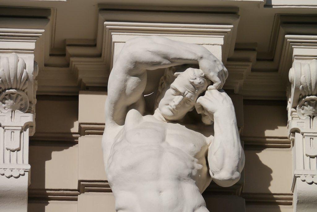 Skulptur eines Mannes an einem Gebäude in Riga.