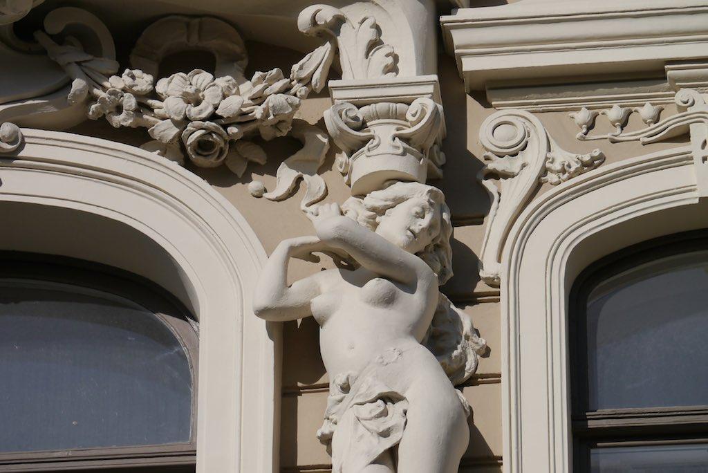 Skulptur einer nackten Frau an einem Jugendstil Gebäude.
