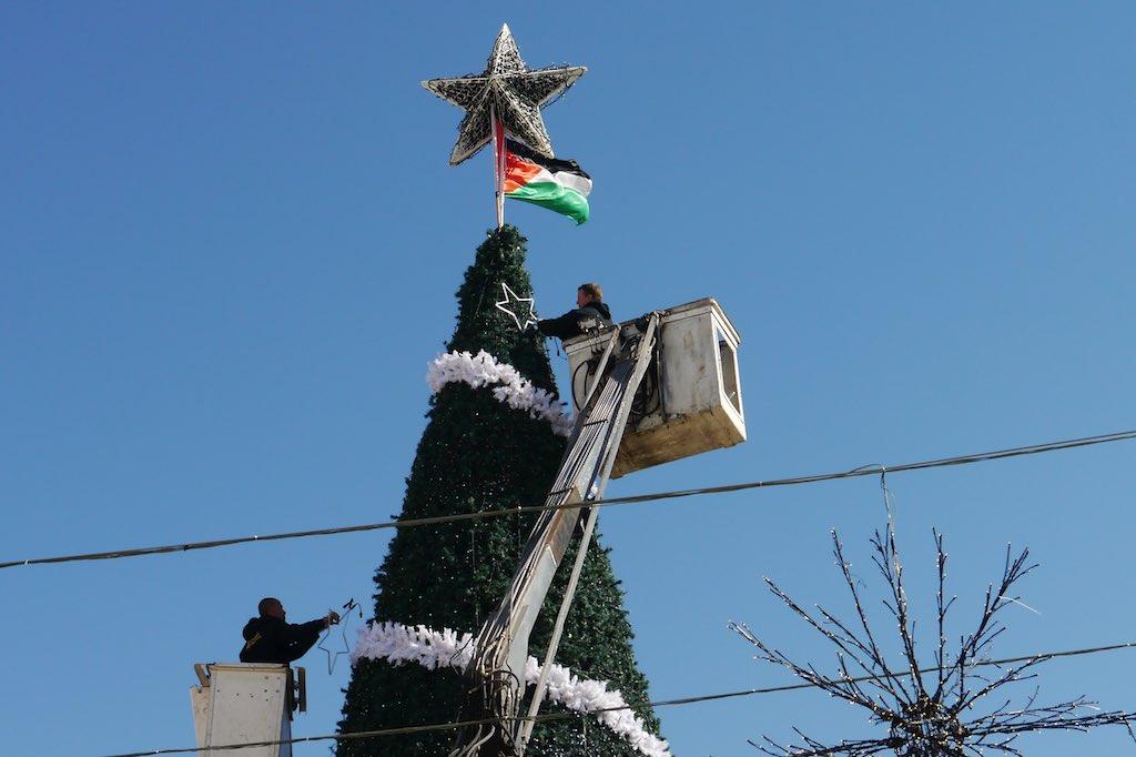 Junge Männer schmücken den Weihnachtsbaum in Bethlehem mit Sternen.