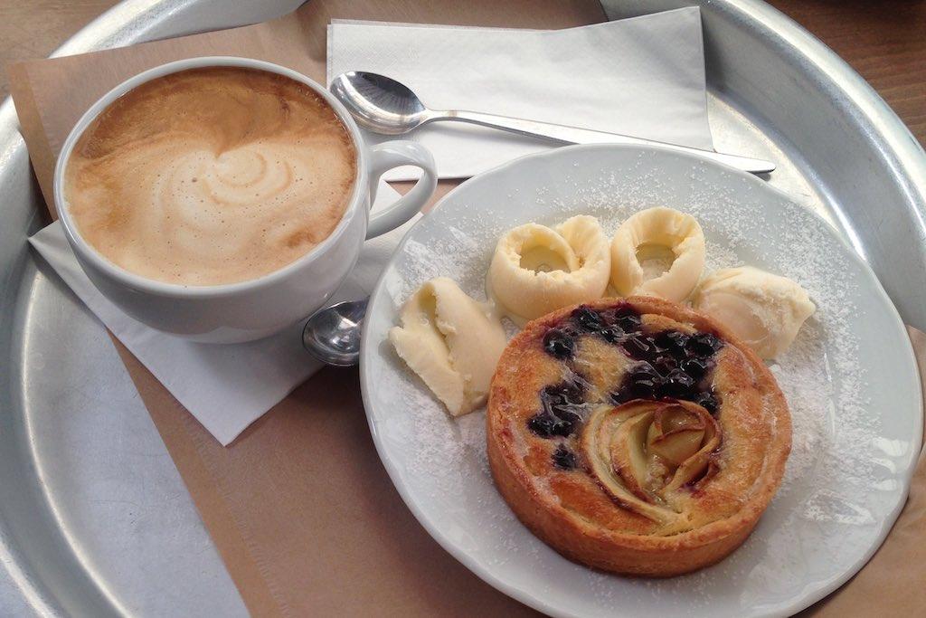 Tarte und Cappuccino auf einem Tablett.