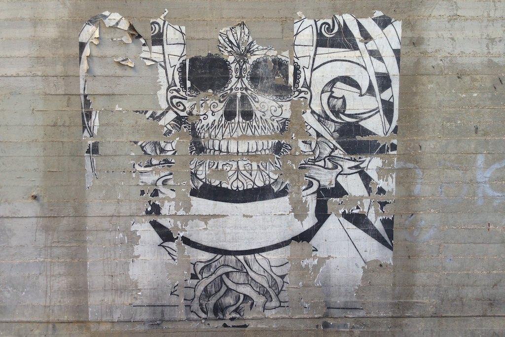 Ein ornamentlare Totenkopf in schwarz/weiß auf einer Sichtbetonwand in Beer Sheva