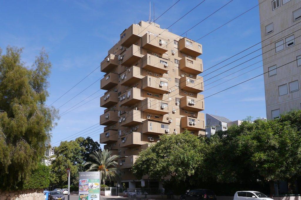 Der Drawer Tower in Beer Shewa. Aus einem Hochhaus auf quadratischem Grundriss ragen über Eck versetze Balkone, die aussehen wie Schubladen.