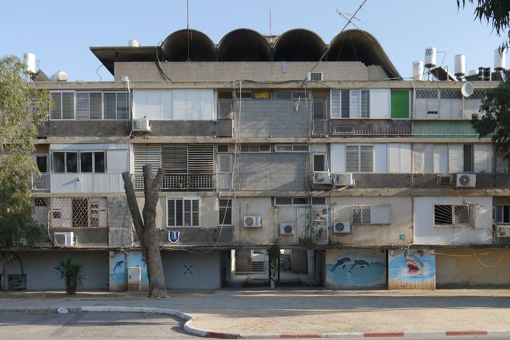 Viergeschossiges Reihenhaus aus den 60er Jahren mit unterschiedlichsten Anbauten aus Blech und Glas. Auf dem Flachdach eine Tonnengewölbte Loggia