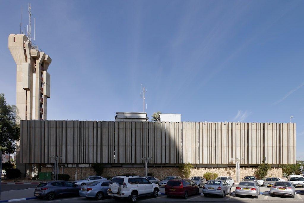 links der Rathausturm von Beer Sheva mit Antennen auf der Spitze. Im Vordergrund der massive Baukörper des Rathauses