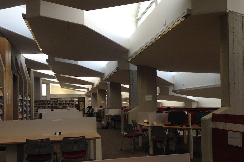 Lesesaal der Universitätsbibliothek. Licht fällt von oben, indirekt auf die Arbeitstische
