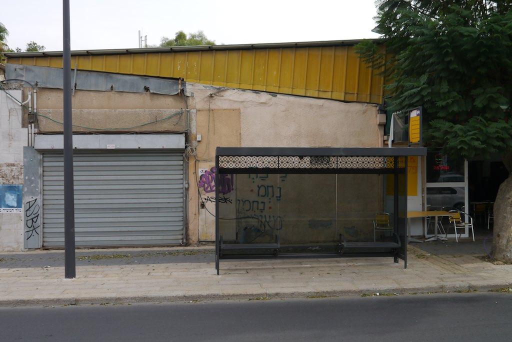 Bushaltestelle in Beer Sheva. Im Hintergrund ein Schuppen aus farbigem Wellblech