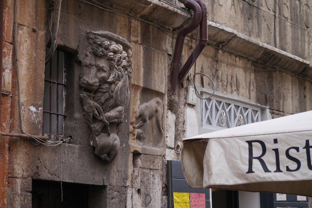 Skulptur eines Löwen in eine Wand eingemauert.