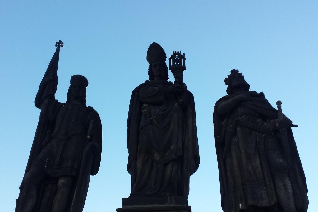 Die steinernen Figuren des Heiligen Wenzel, des Heiligen Norbert und Heiligen Sigismund blicken aus sicherer Distanz auf die Souvenirs-Hölle auf der Prager Karlsbrücke.