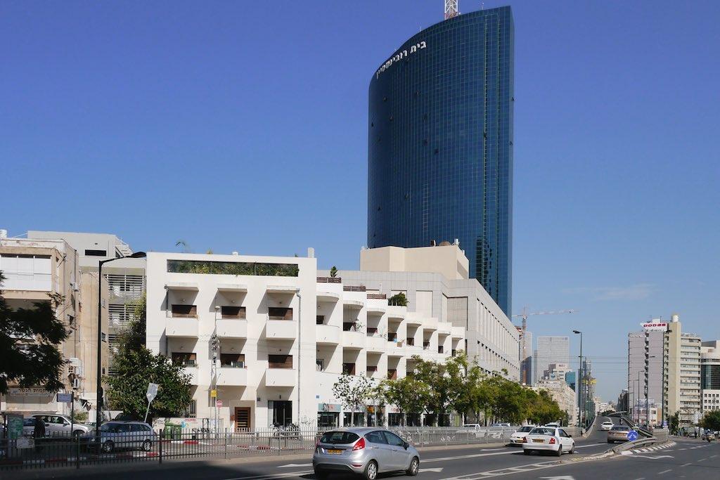 Weiße Bauhaus Architektur vor einem modernen Büro Turm in Tel Aviv.