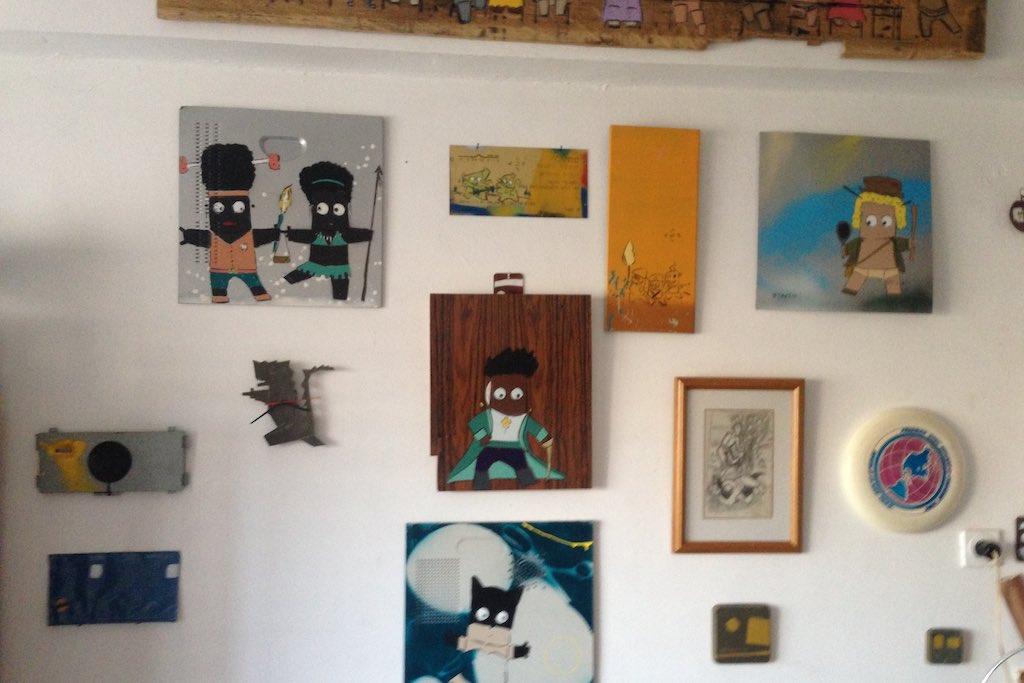 Auf der Wand in Adi Seneds Atelier sind viele kleine Bilder und Skizzen aufgehängt.