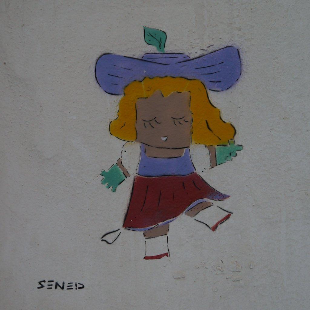 Graffiti von Adi Sened, das eine Frau mit Hut zeigt.