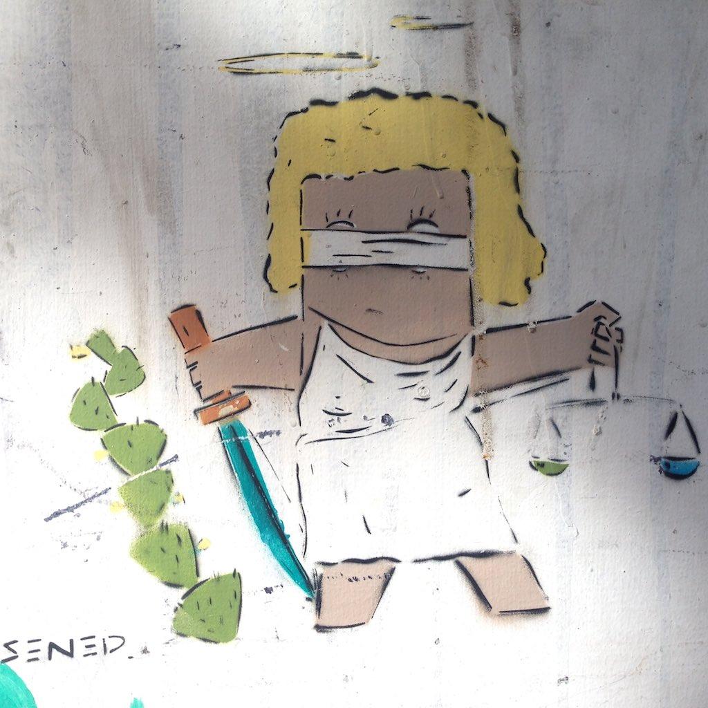 Streetart von Adi Sened, die einen Engel der Gerechtigkeit zeigt