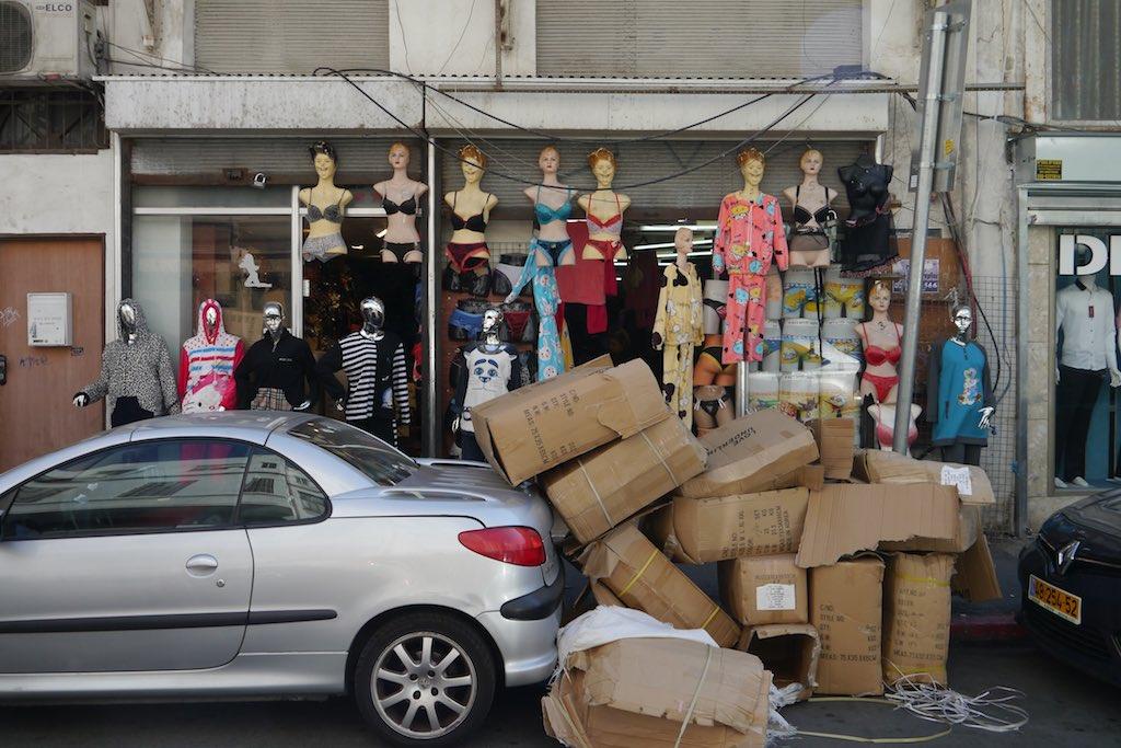 Straßenszene in Florentin. Ein parkendes Auto ist ganz und gar mit Kisten und Kartons zugepackt