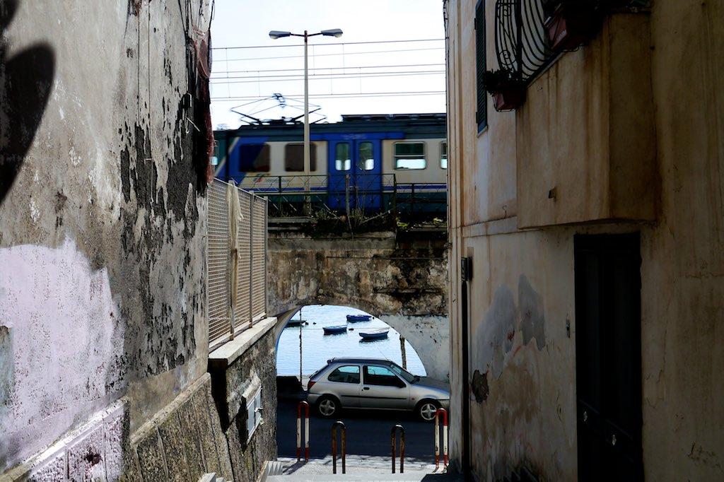 Blick durch einen Bogen des Eisenbahn Viadukts von Torre Annunziata auf das Meer und kleine Boote