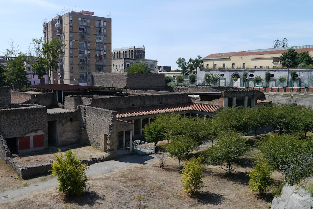 Blick von oberhalb auf die Villa Oplontis. Im Hintergrund ein Hochhaus. Rechts eine alte Kaserne. Im Vordergrund der Garten