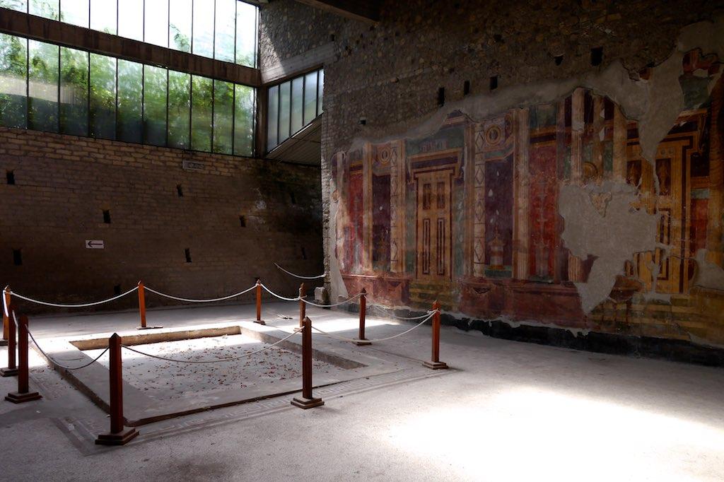 Das Atrium der Villa Oplontis. Die Wände sind mit Theaterarchitektur bemalt. Der Raum wird durch eine moderne Glaskonstruktion geschützt