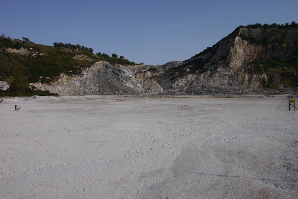 Blick in den Krater des Solfatara Vulkans in Pozzuoli. Der Boden des Kraters ist mit weißer Erde bedeckt. Die Kraterwände sind mit üppiger Vegetation begrünt