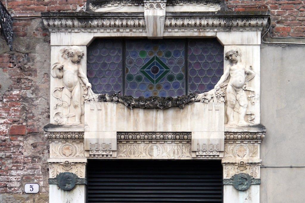 Jugendstil Puten flankieren ein ovales Fenster. Sie halten eine Blumengirlande