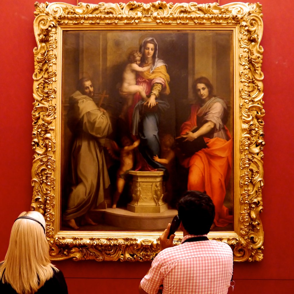 Andrea del Sartos Harpien Madonna hängt in den Uffizien in einem goldenen Rahmen vor einer roten Wand.