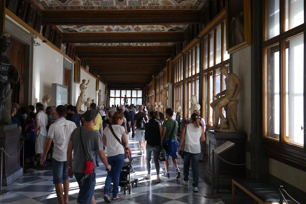 Ein langstreckter Flur in den Uffizien voll mit Museumsbesuchern
