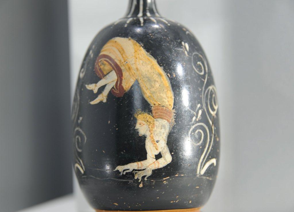 Schwarzgrundige Vase, Gnazischer Produktion, mit einer biegsamen Akrobatin aus dem MARTA in Tarent.