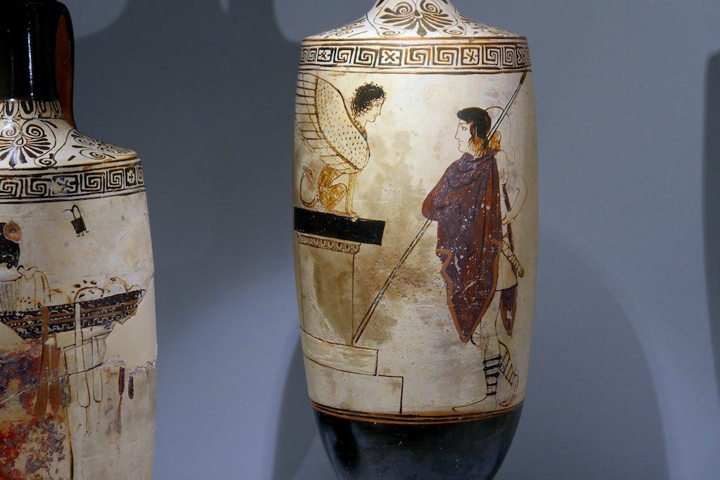 Weißgrundige Vase aus dem MARTA in Tarent. Eine Sphinx auf einem Sockel. Vor ihr steht Ödipus in einem roten Mantel