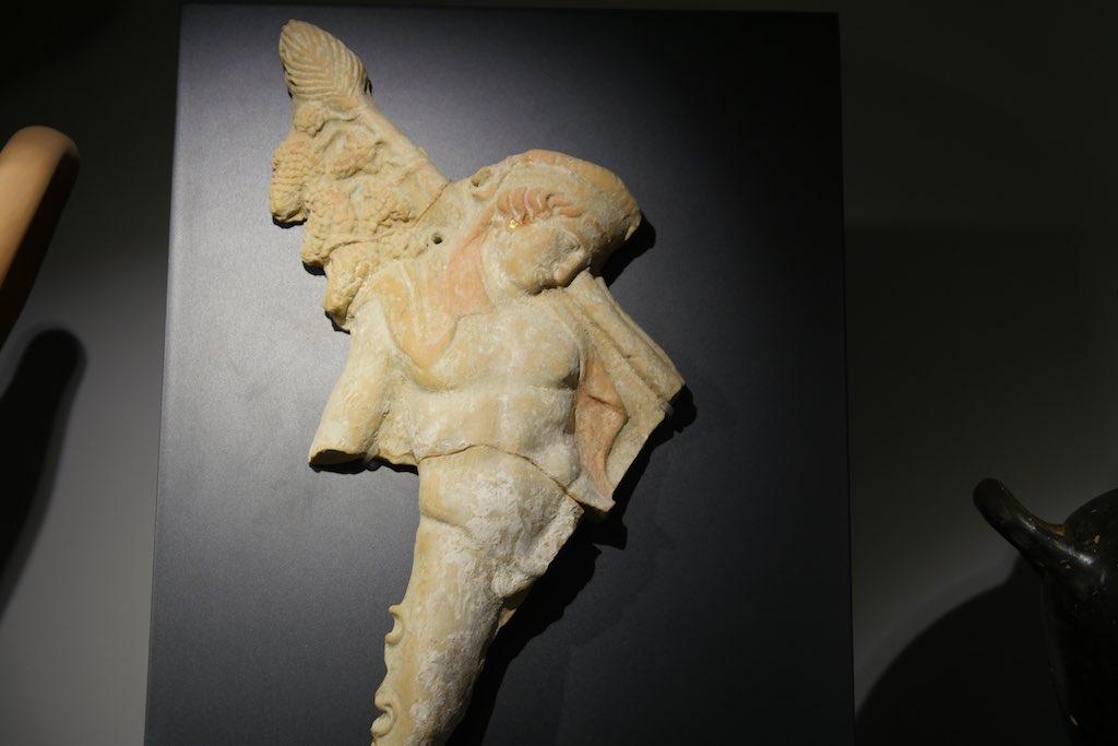 Relief-Fragment mit der Figur des griechischen Weingottes Dionysos. Der Kopf ist geneigt. Der Körper muskulös.