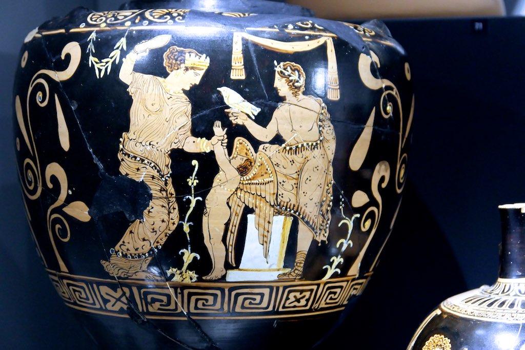 Rotfigurige Vase aus dem MARTA in Tarent. Links steht Venus mit zum Schlag erhobenen Schuh. Sie hält den zeternden Amor an der Hand.