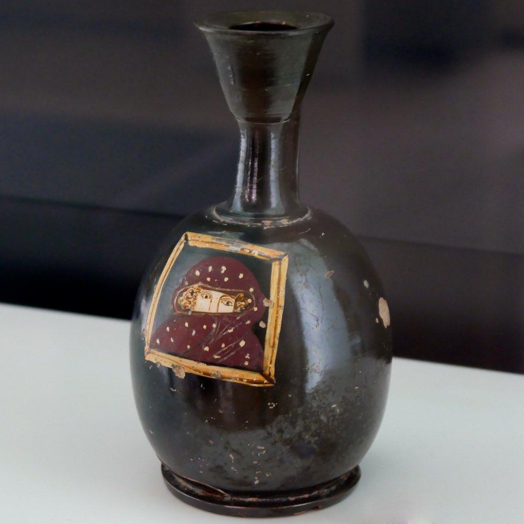 Schwarze Vase aus dem MARTA in Tarent. AUf dem Vasenkörper ist eine verschleierte Dame abgebildet.