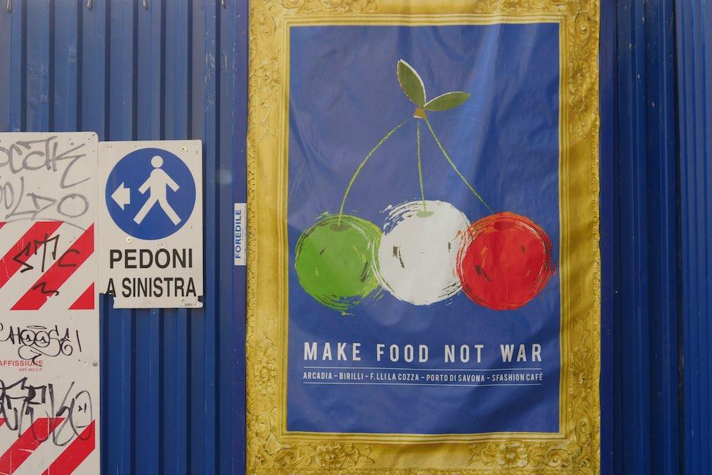 Plakat mit drei Kirschen in Grün, Weiß und Rot mit der Aufschrift Make FoodNo War. Gesehen in Turin.