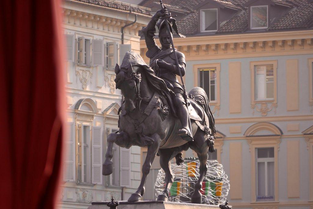 Reiterdenkmal auf der Piazza San Carlo in Turin. Ein Ritter auf dem Pferd steckt sein Schwert in die Scheide. Im Hintergrund barocke Fassaden.