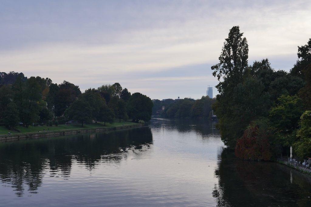 Blick über den Fluss Po in Turin. Links und rechts begrünte Ufer.