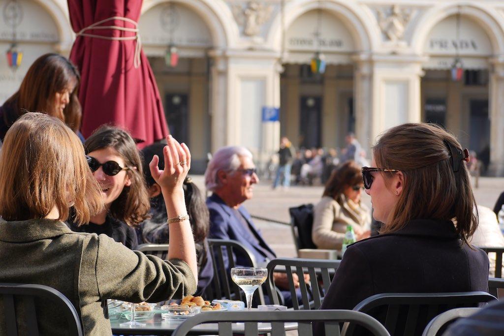 Drei junge Frauen sitzen im Café auf Piazza San Carlo in Turin. Sie trinken Champagner und knabbern gebäck zum Aperitiv