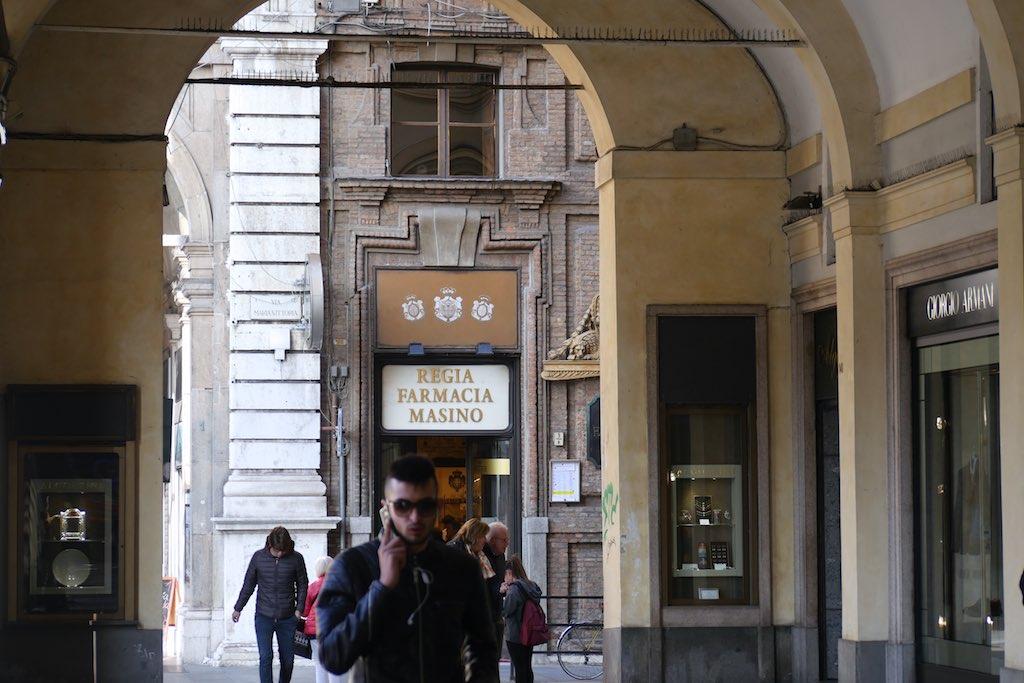 Ein junger Mann mit Sonnenbrille und Handy am Ohr. Typische Straßenszene in Turin.