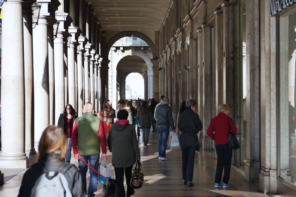 Blick in eine lange Arkade in Turin. Viele Säulen dazwischen hastende Menschen.