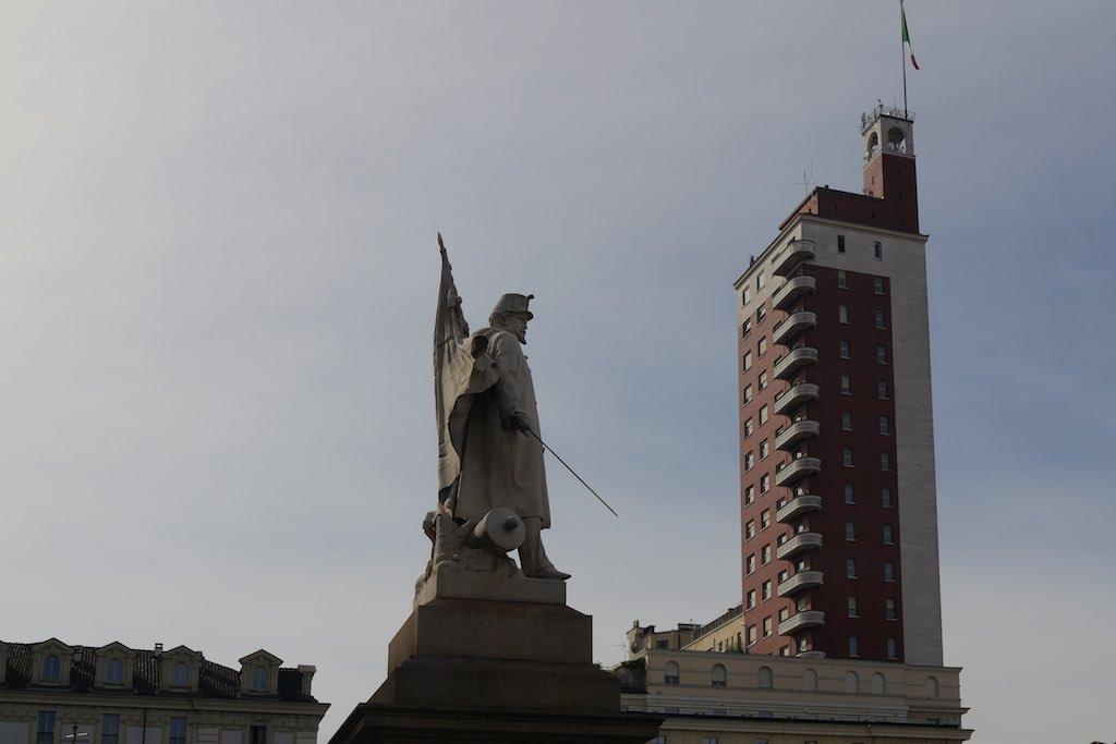 Ein Denkmal mit Soldat, Fahne und Degen auf der Piazza Castello in Turin. Im Hindergrund ein Hochhaus aus Backstein. Auf dem Dach weht die italienische Fahne.