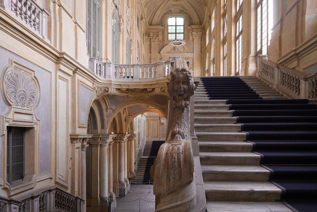 Das Treppenhaus des Palazzo Madama in Turin ist eine typische Barocke Prachtarchitektur. Mehrere Treppenläufe und üppig dekorierte Geländer heben den Besucher in die Höhe. Rechts eine gewaltige Fensterfront.