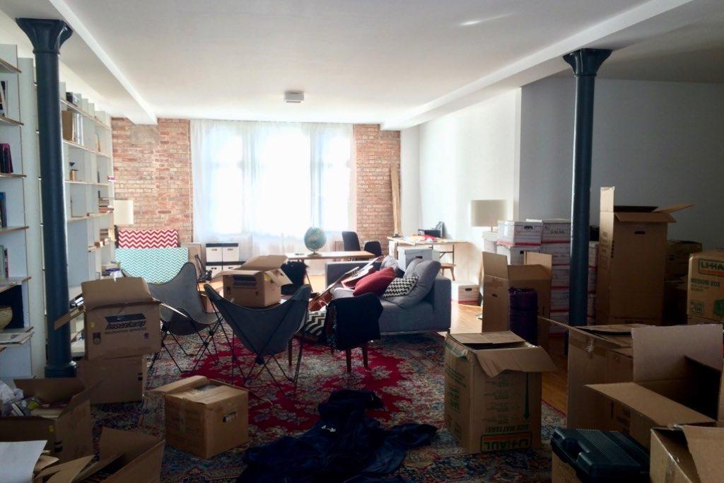 Blick in die neue Wohnung in Stuttgart. Das Wohnzimmer vollgestellt mit Möbeln und Umzugskisten