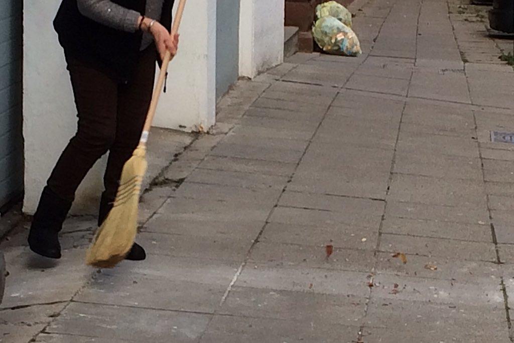 Eine Frau in schwarzer Hose kehrt den Bürgersteig in Stuttgart
