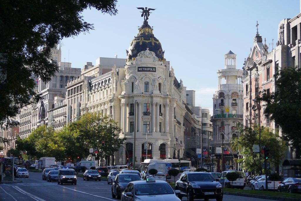 Blick auf ein Eckhaus auf der Gran Via in Madrid. Das weiße Eckhaus ist mit Säulen geschmückt und wird von einer Kuppel gekrönt. Auf dem Gebäude steh Metropolis