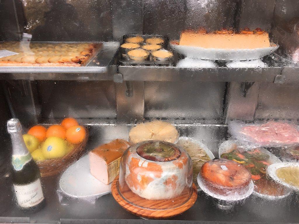 Sektflasche, Apfelkuchen, Pasteten, Fischauflauf hinter einer Glasscheibe. Schaufenster eines Restaurants in der Nähe des Museo Reina Sofia