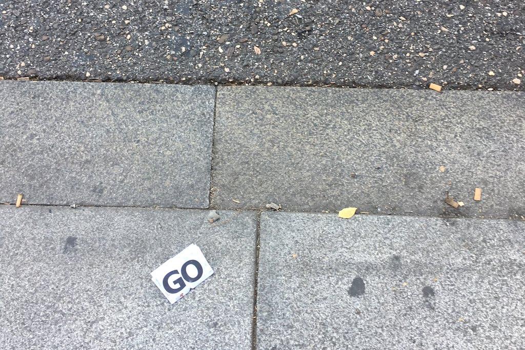 """Straßenpflaster in Madrid, auf dem ein kleiner Zettel mit der Aufschrift """"Go"""" liegt."""