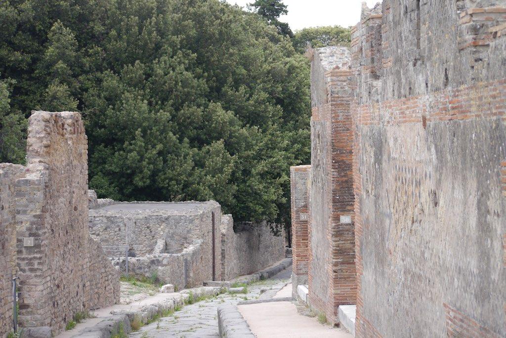 Blick eine Straße in Pompeji herunter. Links und rechts grau verputze Mauern.