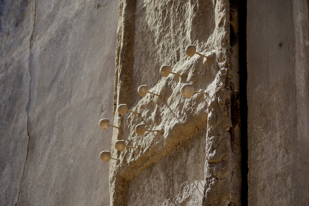 Bronzenägel ragen aus einem Türflügel heraus.