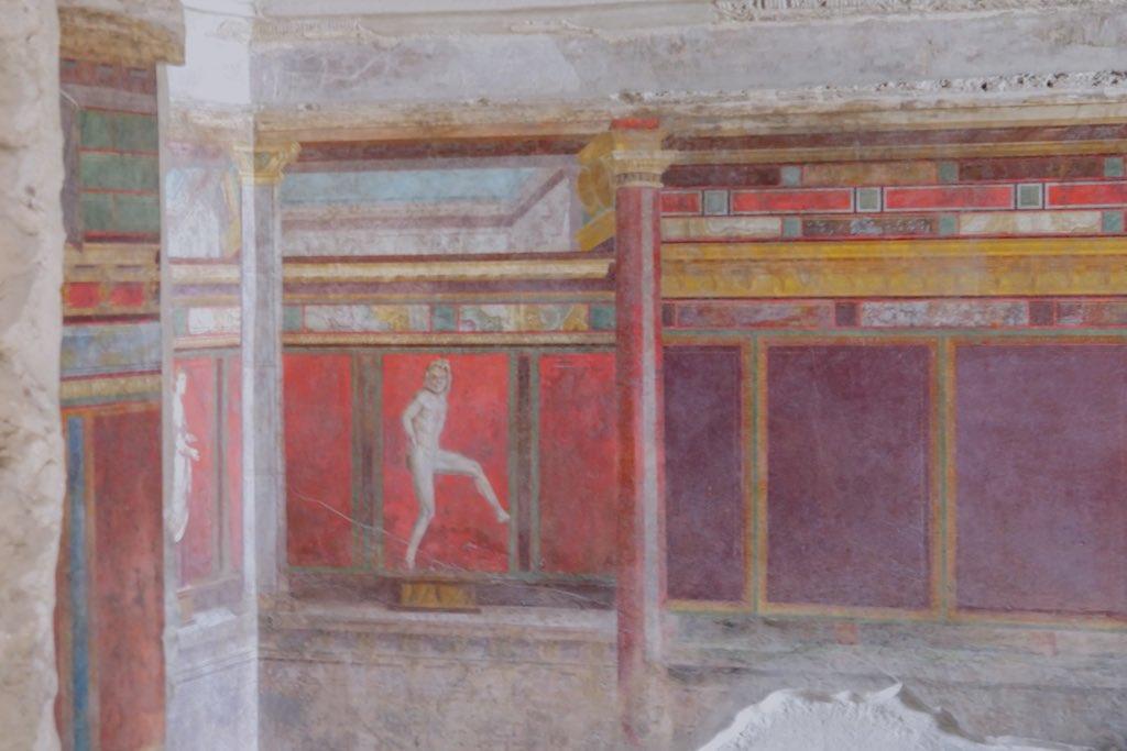 Architektonisch gegliederte Wandmalerei mit kräftigem pompejanischen Rot, himmelblau, violett und gelb.
