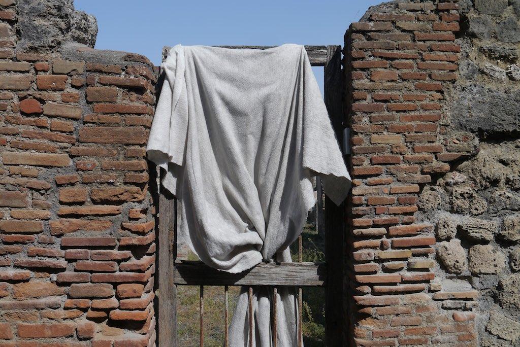 Backstein Mauer in Pompeji mit einer Gittertür verschlossen.