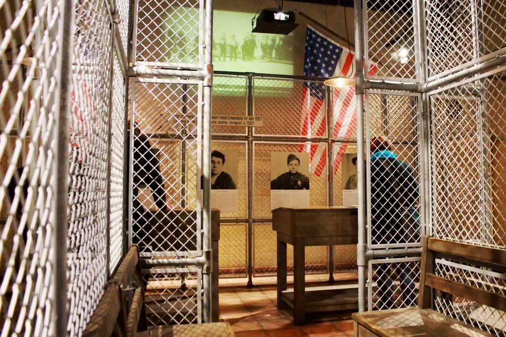 """Wir Auswanderer: Abfertigung der Einwanderer auf Ellis Island. Der """"Registry Room"""" und seine Ausstattung sind originalgetreu wiedergegeben. Über ein Tonband ertönen Glockenschläge. Jeder einzelne erinnert an einen Einwanderer im Jahr 1907."""