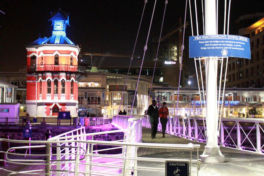 Mother City: Nächtliche Illumination an der V & A Waterfront. Links ist der historische Clock Tower zu sehen. Gleich daneben fahren die Fähren zur ehemaligen Gefängnisinsel Robben Island.