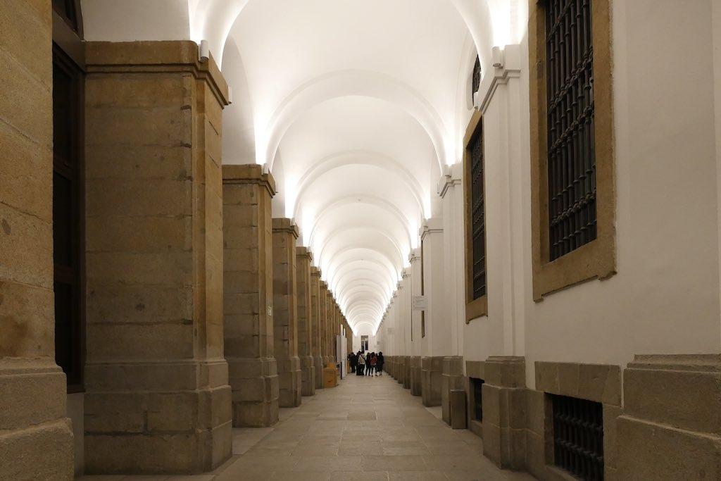 Langer Flur im Museo Reina Sofia. Pfeiler aus Kalkstein und weißgetünchte Decken.
