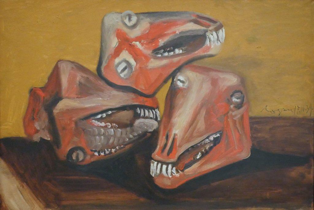 Stillleben von Pablo Picasso. Drei rot gemalte Lammschädel liegen auf einer braunen Tischplatte vor einer gelben Wand.